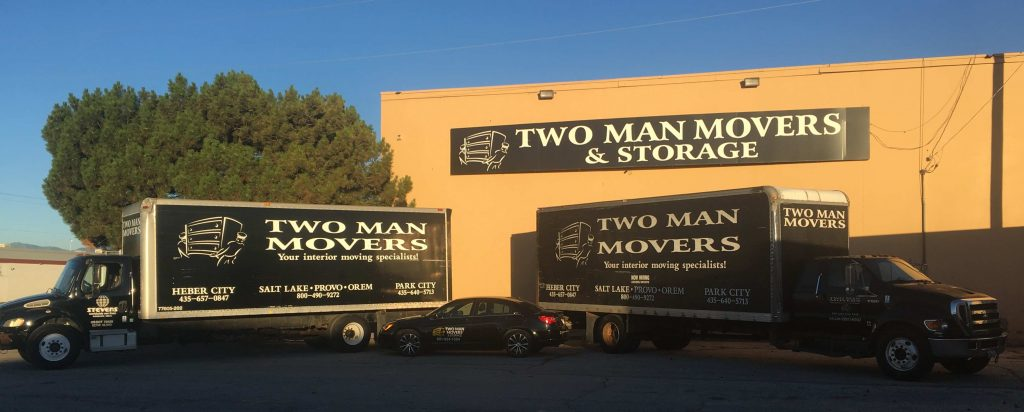 Two Man Movers moving trucks and building sign